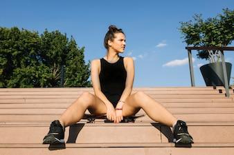Bela mulher sentada no skate ao longo da escada