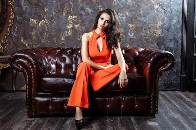 Bela mulher sentada no sofá antigo