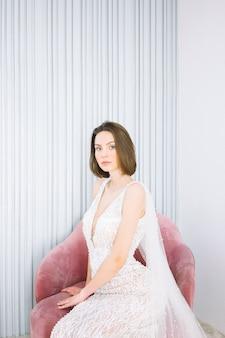 Bela mulher sentada num sofá e olhando no quarto com paredes brancas em vestido longo branco