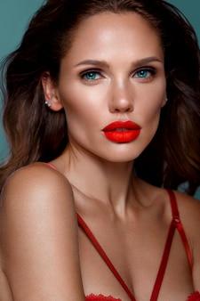 Bela mulher sexy à maneira de hollywood com cachos, maquiagem natural e lábios vermelhos, rosto e cabelo de beleza