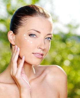 Bela mulher sexy aplicando creme cosmético na pele perto dos olhos - ao ar livre