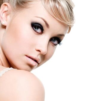 Bela mulher sexy com maquiagem de olho roxo. rosto de close-up isolado no branco