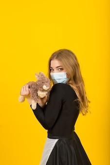 Bela mulher sexy com roupa de empregada, posando com o brinquedo de coelho em uma máscara protetora cobiçada
