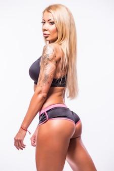 Bela mulher sexy de fitness mostrando músculos sobre o branco