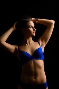 Bela mulher sexy em cueca azul em uma parede escura, corpo feminino perfeito, estúdio tiro