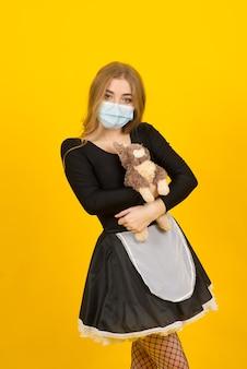 Bela mulher sexy em roupas de empregada, posando com o brinquedo de coelho em uma máscara protetora cobiçada