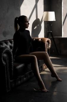 Bela mulher sexy em sofá de couro em quarto escuro