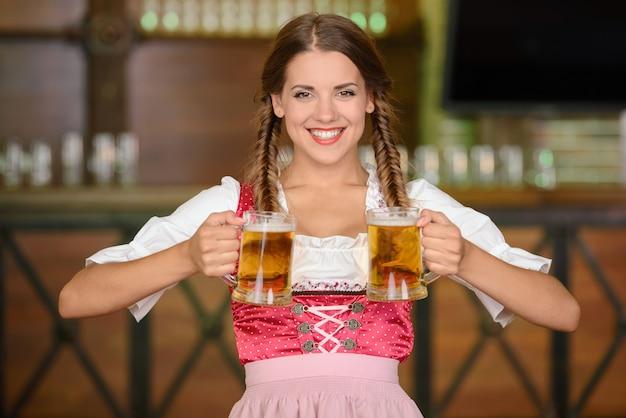 Bela mulher sexy garçom segurando copos de cerveja.