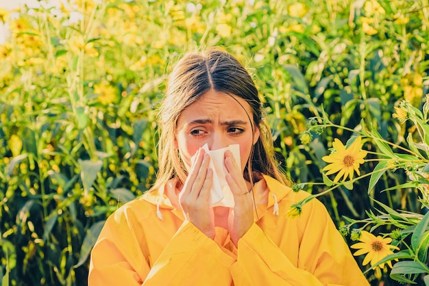 Bela mulher sexy jovem encontra-se em flores. jovem espirrando e segurando um lenço de papel