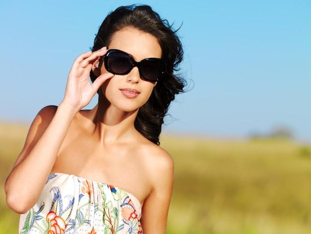 Bela mulher sexy na natureza em óculos de sol pretos
