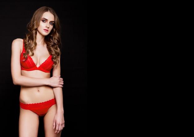 Bela mulher sexy vestindo lingerie chique vermelha