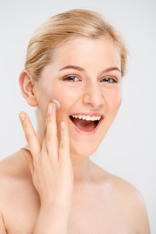 Bela mulher sorridente aplicar creme facial