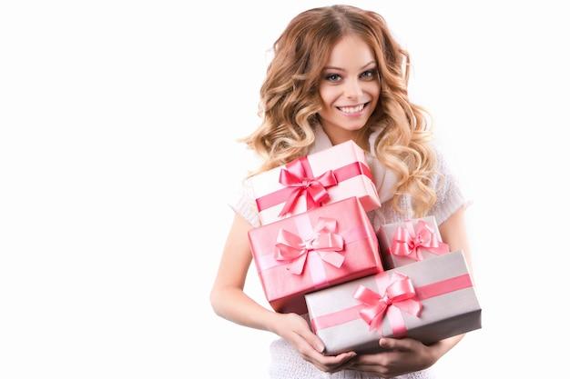 Bela mulher sorridente com cabelo encaracolado segurando presentes isolados no fundo branco.