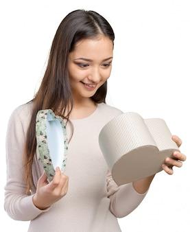 Bela mulher sorridente com cabelos longos, segurando a caixa de presente