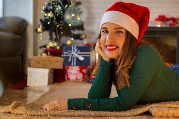 Bela mulher sorridente com chapéu de natal, deitado no tapete ao lado da árvore de natal e presentes