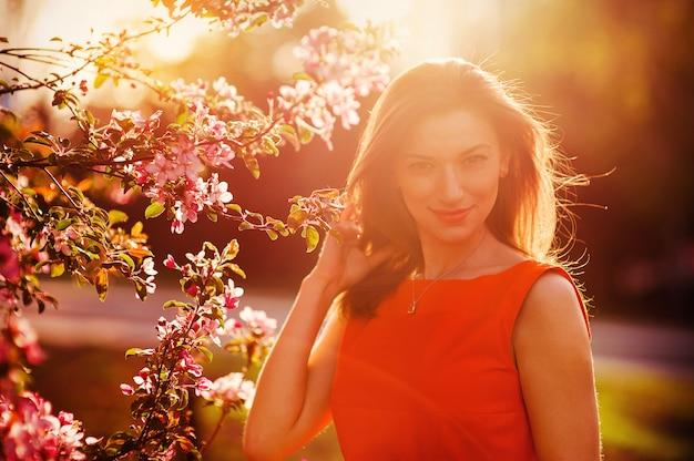 Bela mulher sorridente com flores da primavera