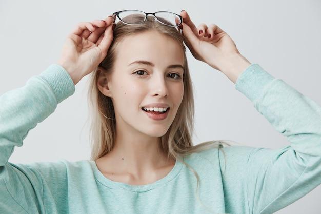 Bela mulher sorridente, com longos cabelos loiros e óculos elegantes, tem aparência europeia, parece deliciosamente