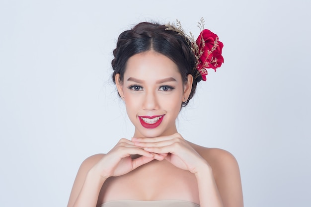 Bela mulher sorridente com pele fresca limpa e flor no cabelo