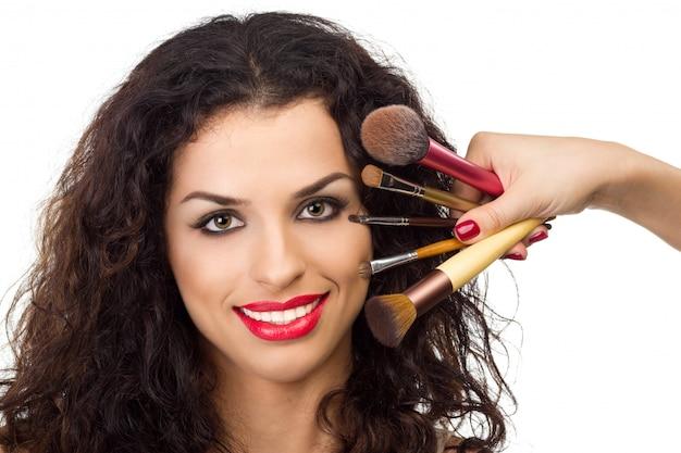 Bela mulher sorridente com pincéis de maquiagem perto do rosto