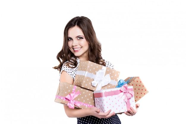 Bela mulher sorridente com presentes no vestido de bolinhas.