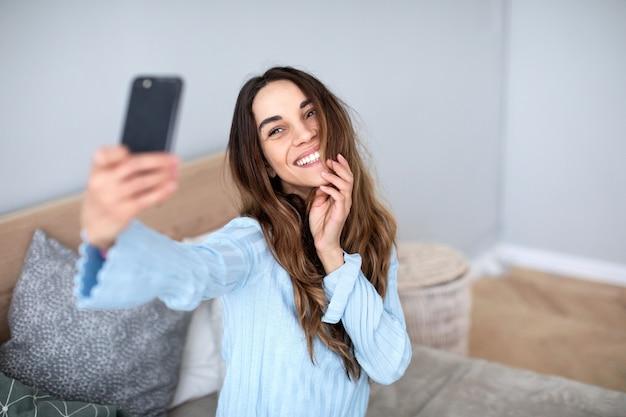 Bela mulher sorridente com um telefone tira uma selfie em casa. estilo de vida.