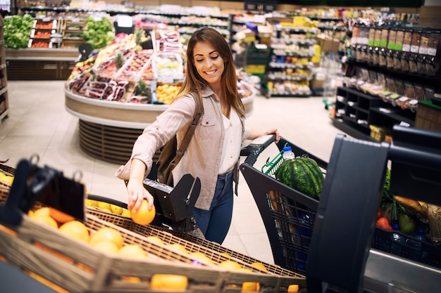 Bela mulher sorridente comprando laranjas em um supermercado na seção de frutas