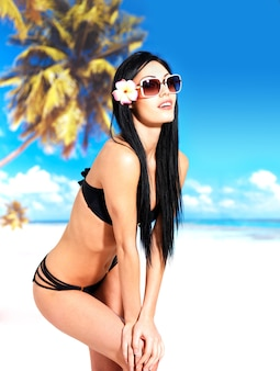 Bela mulher sorridente de biquíni na praia.