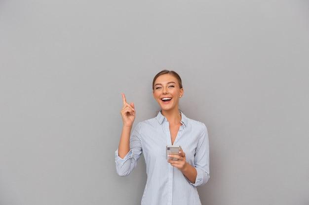 Bela mulher sorridente de negócios em pé sobre o fundo da parede cinza, usando o telefone móvel apontando.