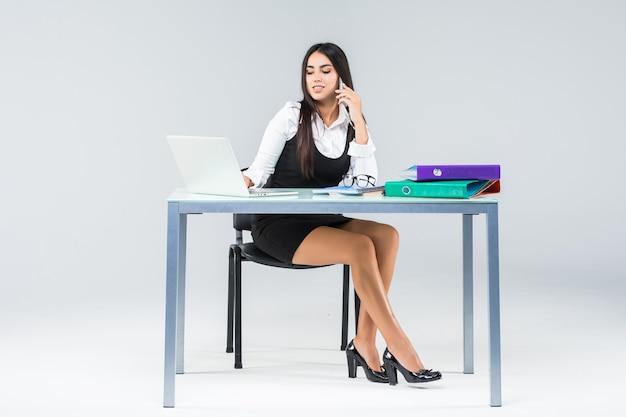 Bela mulher sorridente de negócios se senta na mesa e trabalhando no laptop na camisa branca isolada no branco.
