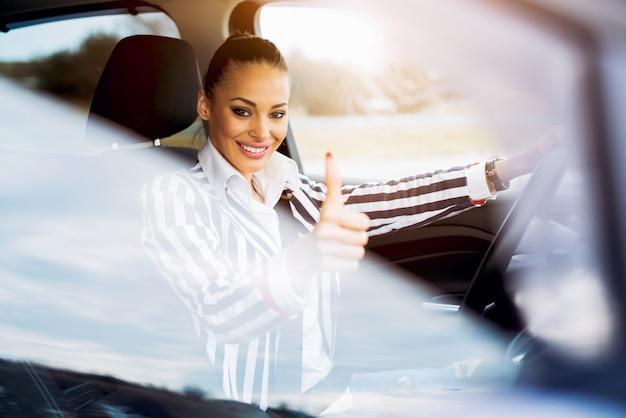 Bela mulher sorridente dirigindo um carro aparecendo polegar.
