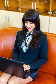 Bela mulher sorridente em um terno sentado em um escritório no sofá com o laptop