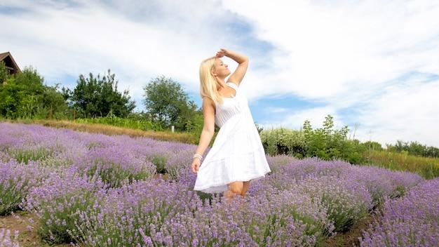 Bela mulher sorridente em um vestido branco, olhando no campo de lavende grande em provence.