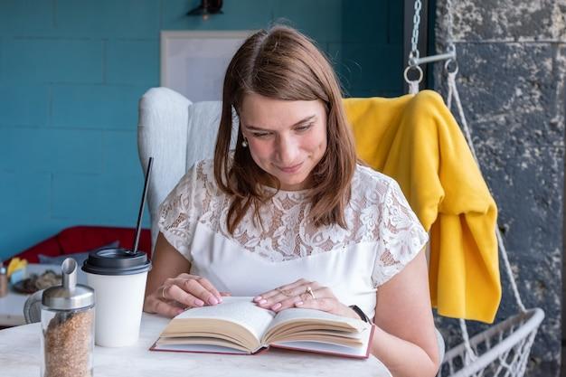 Bela mulher sorridente está bebendo café e lendo um livro enquanto está sentado em um café.