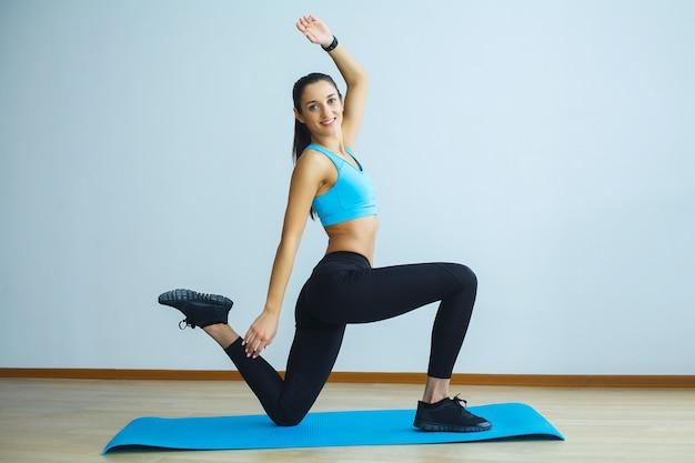Bela mulher sorridente fazendo yoga dentro de casa no ginásio