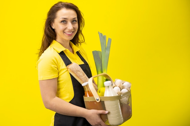 Bela mulher sorridente fica do lado do lado com caixa de verduras, leite, ovos, pão