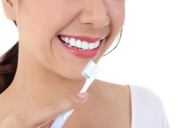 Bela mulher sorridente, limpa os dentes brancos, lábios cor de rosa, segura uma escova de dentes.