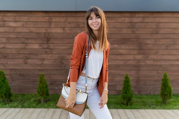 Bela mulher sorridente na jaqueta posando na cidade.