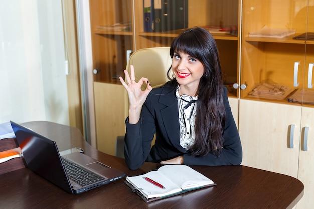 Bela mulher sorridente no escritório mostrando o símbolo bem