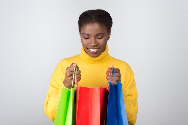 Bela mulher sorridente, olhando na sacola de compras