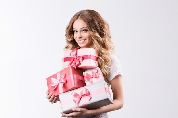 Bela mulher sorridente segurando um presente em fundo branco.