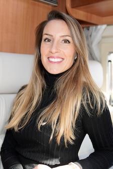 Bela mulher sorridente, sentado à mesa no motor rv campervan van em casa no conceito de estilo vanlife