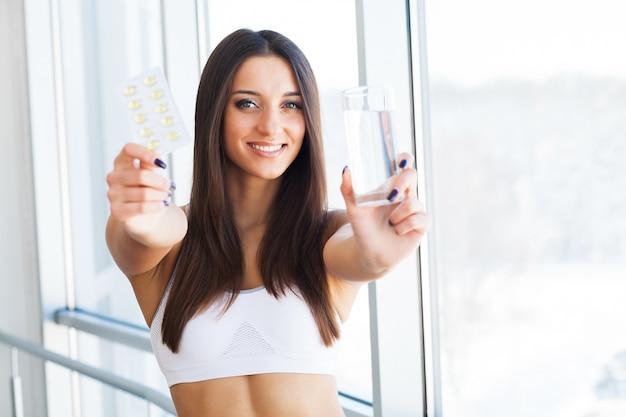 Bela mulher sorridente tomando comprimidos de vitamina e copo de água