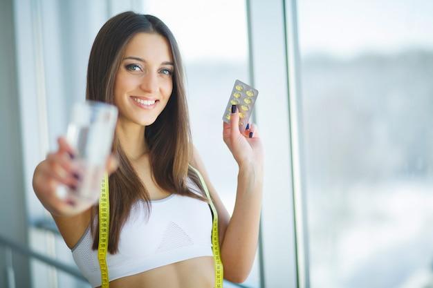 Bela mulher sorridente tomando pílula de vitamina. suplemento dietético