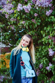 Bela mulher sorridente usando fones de ouvido amarelos sob o arbusto lilás