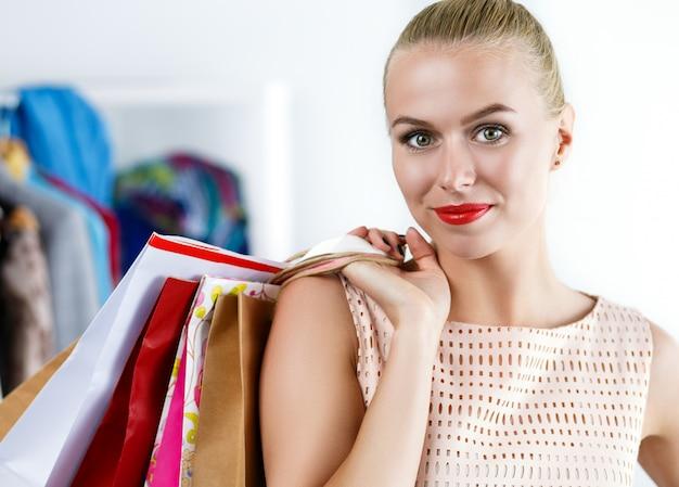 Bela mulher sorridente, vestido, segurando os sacos de papel colorido atrás de seu retrato de ombro