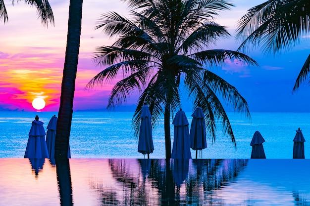 Bela natureza ao ar livre paisagem com mar oceano e coqueiro ao redor da piscina no sunrsie ou pôr do sol
