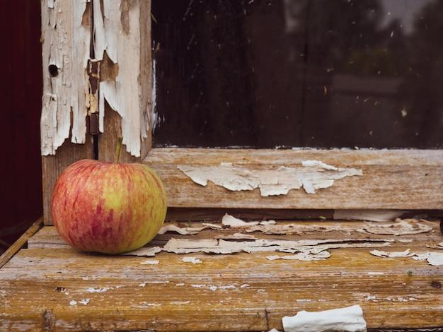 Bela natureza morta rústica, maçã madura no parapeito de uma janela velha