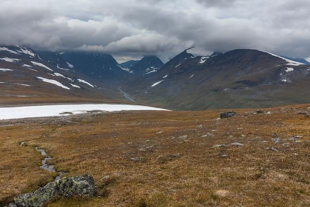 Bela natureza selvagem do parque nacional de sarek, na lapônia sueca, com montanhas cobertas de neve, rio e lago
