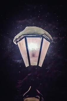 Bela noite de inverno com a lâmpada de rua brilhando na neve