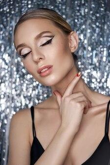 Bela noite de maquiagem nos olhos de uma mulher loira em um brilhante